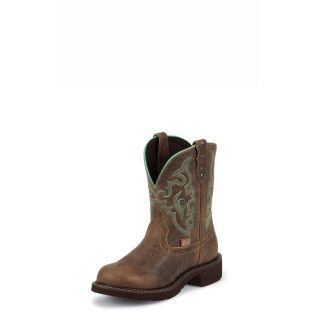 """The 8-inch tall Gemma Brown Short Justin Gypsy™ Women's cowboy boot is a modern take on a vintage classic. The distressed chocolate brown leather exterior provides a lived-in look while the sea green stitch pattern and the matching seam on the collar is a subtle nuance that gives this boot an edge. The round toe and unit heel provide a relaxed fit and the J-Flex Flexible Comfort System® insole with removable orthotic inserts guarantees lasting comfort for the cowgirl on the go.  8"""" TAN…"""