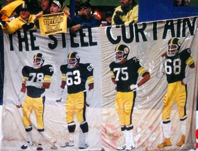 """The Steel Curtain Four referred to the four defensive tackles of the Pittsburgh Steelers – there was Joe Greene, L.C. Greenwood, Ernie Holmes and Dwight White. The team got their nickname from a 9th grader who had submitted the name """"Steel Curtain"""" through a contest entry at a local radio station. The Steel Curtain Four became the first dominant all-black starting four in league history."""