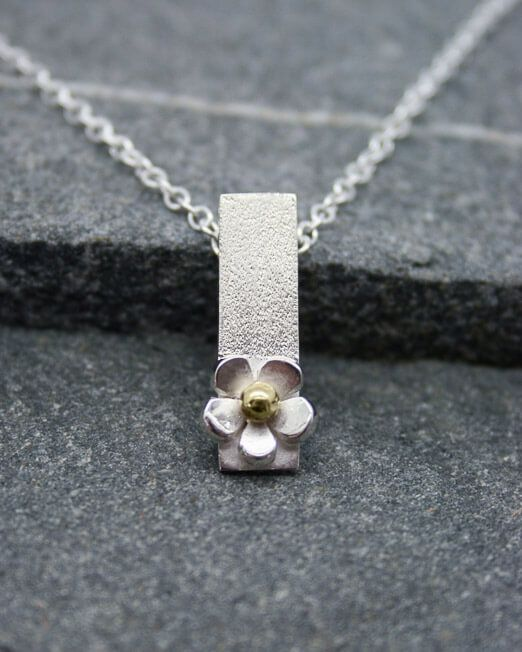 "Handmade silver daisy drop necklace with a brass centre.  The pendant measures 21 x 6mm. with a satin finish to the bar and features a hand saw pierced silver daisy with a single brass bead centre.  Necklace is supplied with a sterling silver 16 or 18"" chain.  #Daisy #HandmadeJewellery #MixedMetal #Necklace #Pendant #Starboard"