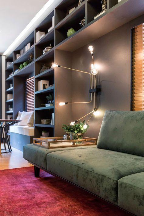 Decoração neutra e elegante, Casa Cor, na sala estante preta com nichos e adornos, parede cinza, luminária de parede, tapete vermelho, plantas na decoração e lareira em mármore.