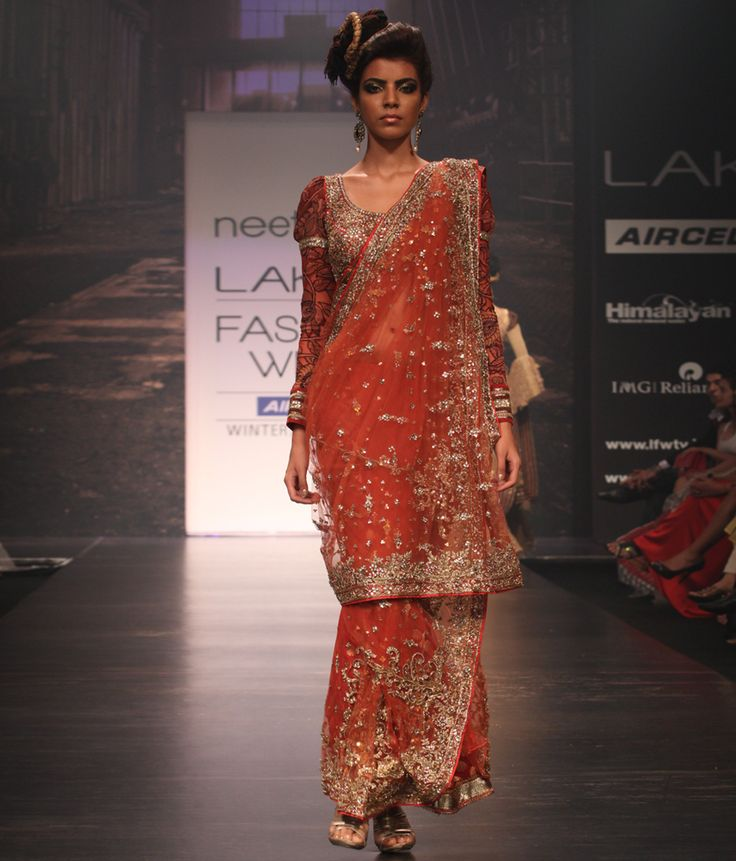 Neeta Lulla A beautiful rust coloured net saree embellished with hand embroidery and sequin butis all over and hand embroidered, sequin and stone work borders. The saree comes with a matching blouse with kundan work and full length leg 'o mutton, kalamkari sleeves.<br><br><b>Disclaimer :</b> There might be a slight variation in the lace and applique patches used.