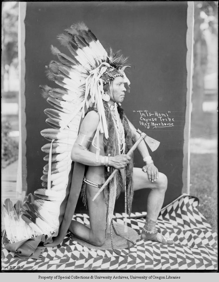 A Native American man, identified as Tots-homa of the Cayuse tribe, is kneeling outside on one knee. He is wearing a single trail bonnet, earrings, a loop necklace, bracelets, and moccasins. He is holding a hatchet-style pipe in his right hand. He is kneeling on a coiled cedar root mat. A Pendleton blanket is underneath the mat. A studio backdrop is behind him. Photo by Major Lee Moorhouse
