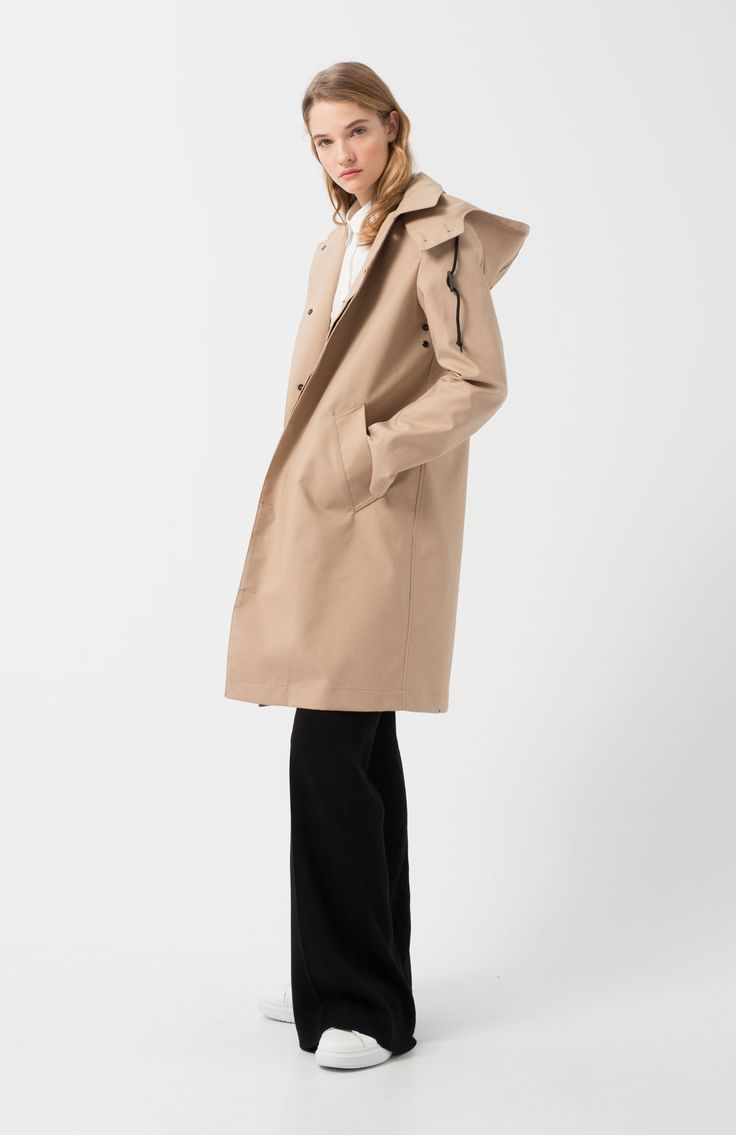 Ura beige raincoat. Beige timeless raincoat. Front flap pockets. Neck with removable hood. Waterproof fabric from the brand British Millerain, rigid but malleable. Long and regular fit. Loreak Classic.