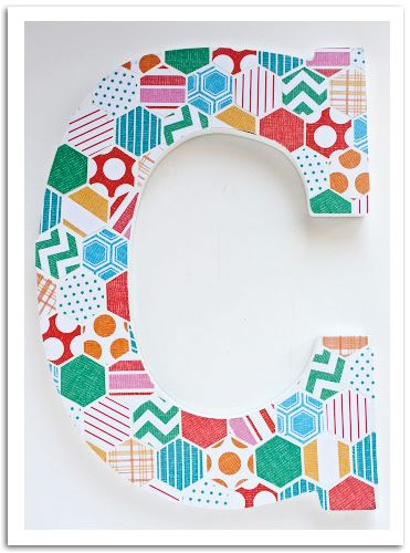 Apply scrapbook paper cut into hexagons pieces on a monogram letter. X-ACTO knife will be handy for this project.