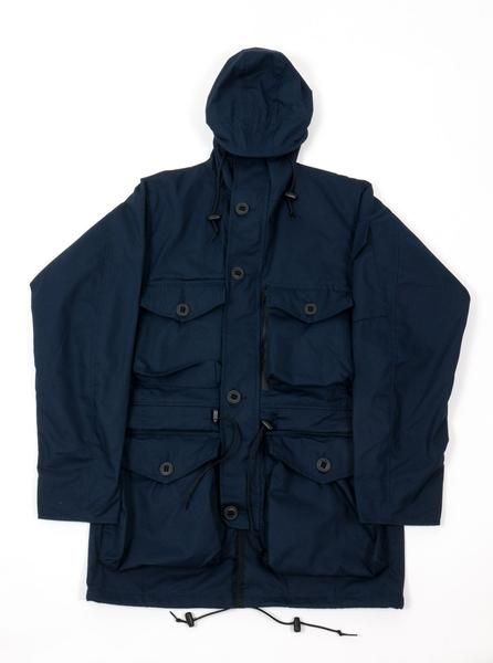 ArkAir - B601AA - Waterproof Combat Smock - Navy Blue  Material: 50% cotton / 50% polyester Water Resistant Ripstop fabric Drawstring hood withwire frame Hood with adjustable back button Velcro neck fastening Two way front zip closurewith button through storm flap Four large front pockets Two zip concealed chest pockets Sleeve pocket Drawstring waist and hem Adjustable button cuffs Fully lined Made in England   ArkAir was born out of the Arktis Group in 2014. Central to the ArkAir project…