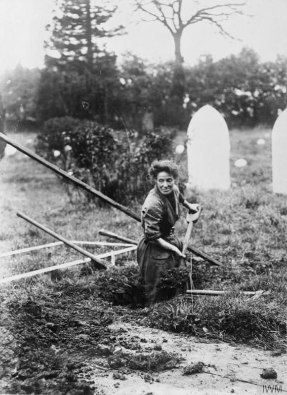 Mrs Kitchener, a female gravedigger, carries on her husband's business whilst he serves on the front, Aley Green Cemetery, Luton. Filling the grave. 1914-1918