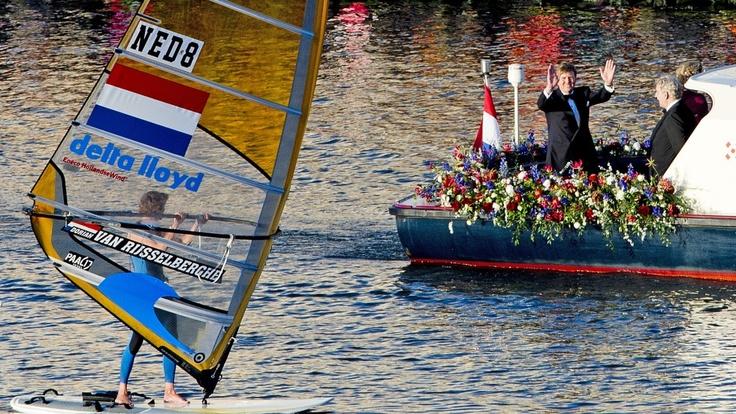Het koninklijk gezelschap zwaait tijdens de koningsvaart op het IJ naar windsurfer Dorian van Rijsselberghe.