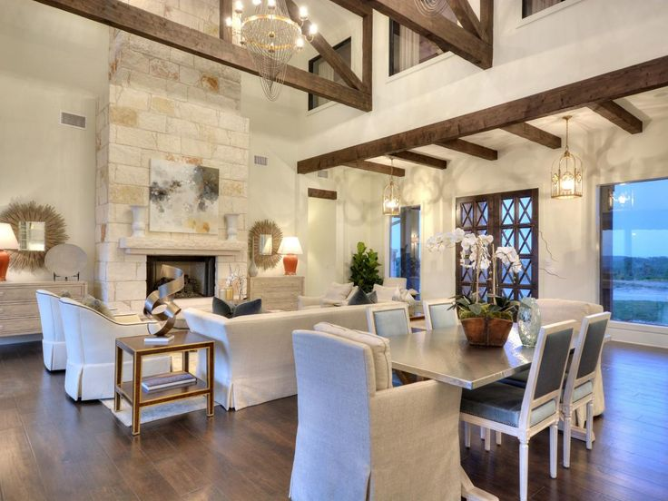 The open layout of this spectacular great room allows for seamless entertaining from the casual dining space into the living area. Exposed beams contrast beautifully with the white walls and emphasize the high ceiling. Chic neutral furnishings provide plenty of seating around the tall, stone fireplace.