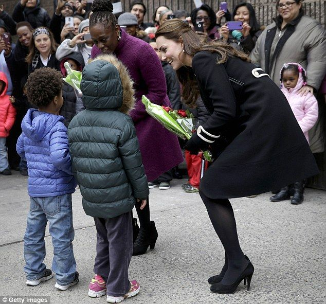 Kid-approved: Five-months-pregnant Kate greets children outside the Harlem center with May...