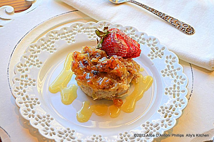 'Coconut Strawberry Bread Pudding'    That would be velvety Whiskey Sauce and drunken berries,  What you need:    1 tbl butter    1 cup milk    1 cup coconut milk    2 eggs    1/2 cup plus 2 tablespoons sugar, plus extra for spooning in the base of the muffin tin    1 teaspoon vanilla extract    ¼ cup golden raisins    ¼ cup sweetened coconut    2 ½ to 3 cups day-old French bread, torn or cut into bite-sized pieces    12 whole strawberries    ¼ cup whiskey