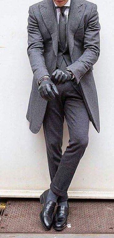 Él lleva una gris trage. También él lleva gris guantes y negro elegante zapatos. Él traje de ropa cuesta treinta y uno dólares.