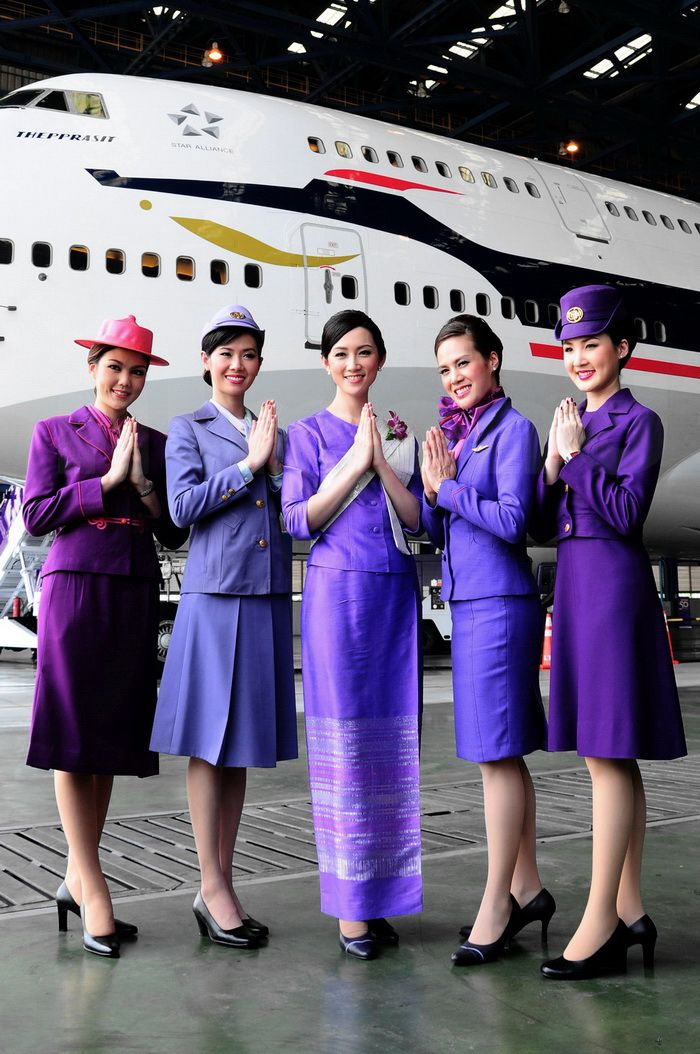 About 15 years ago I dropped a friend off at LAX. As I was driving away, five Thai Airways flight attendants crossed the busy street (dressed like the woman on the right). For the 30 seconds it took them to cross, everything STOPPED. Traffic, people...EVERYONE stopped what they were doing to watch. I don't know much about uniform design, but when you can shut down one of the busiest airports in the world with clothing? You've done something right. Striking.
