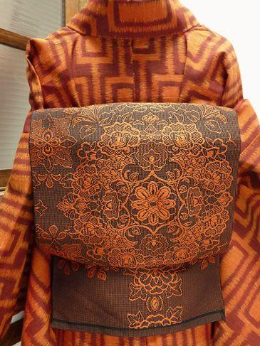 ブラウンとオレンジで織り出された、レースを重ねたような繊細で優美な装飾模様がロマンチックな詩情をさそう開き名古屋帯です。