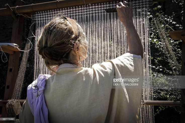 A woman weaving on a vertical loom. Roman Italy. Historical reenactment.