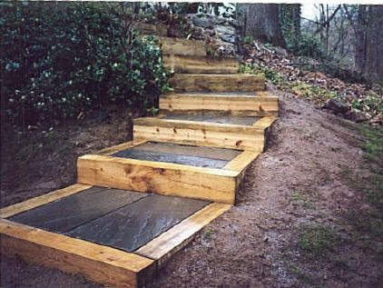 Flagstone steps with wood tie risers. Ties are staked to the ground with 2' reinforcing rods and ...