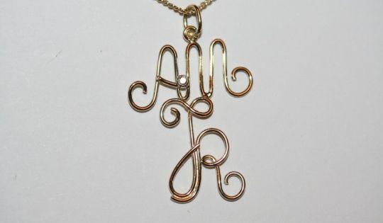 Draad hanger geelgoud met letters A, M en R, gemaakt door Atelier DOS