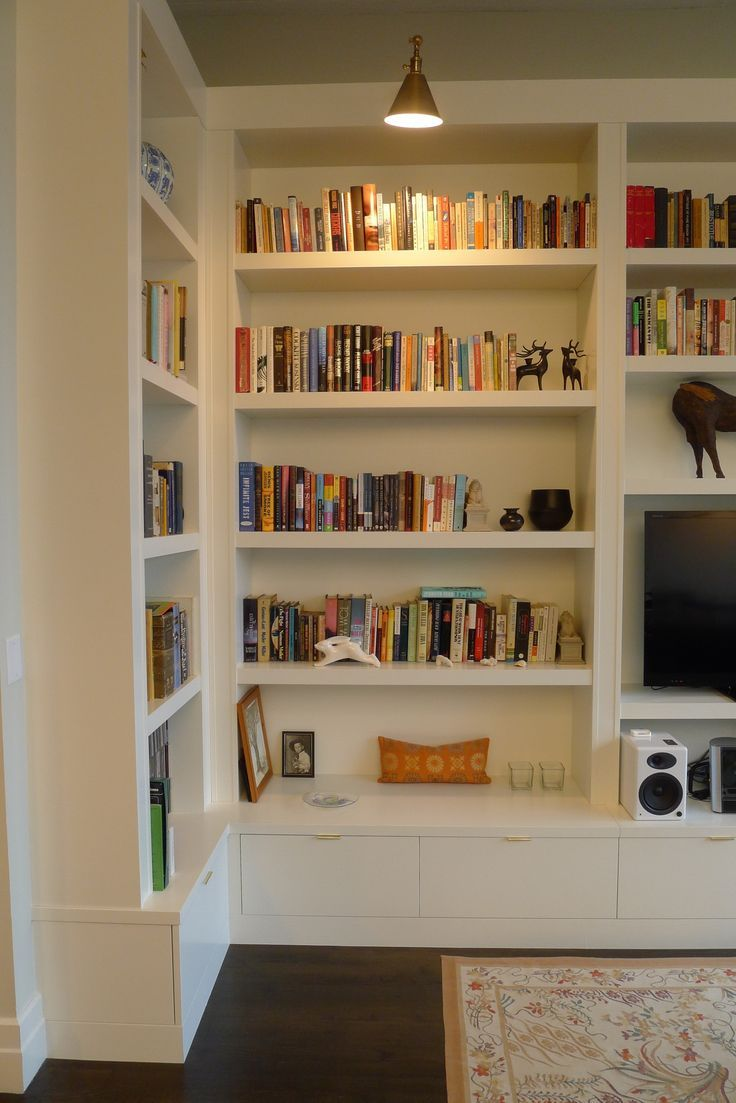 A Wall Of Custom Designed Shelving Was Added To This Apartment Bookshelves In Living Room Shelving Units Living Room Media Room Design