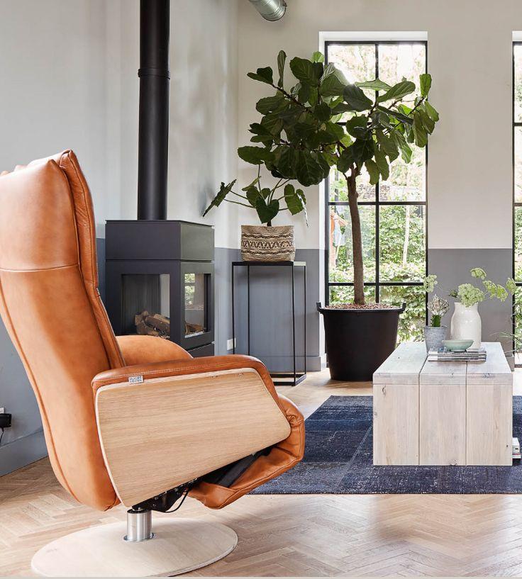 Creëer warmte in jouw industriële interieur door een fauteuil in cognackleurig leer, houten meubels en een zacht vloerkleed!