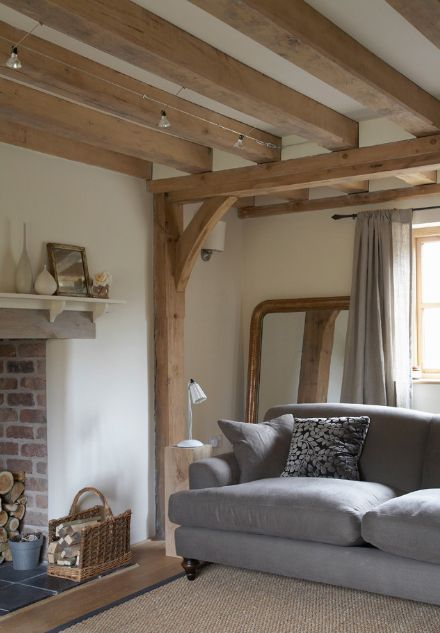 Light wood beams, gray sofa, brick fireplace. And... is that plaster wall?