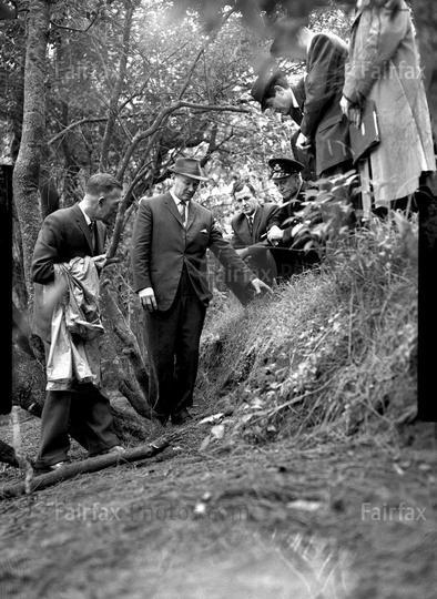 Detectives and the coroner at the Bogle Chandler murder scene.