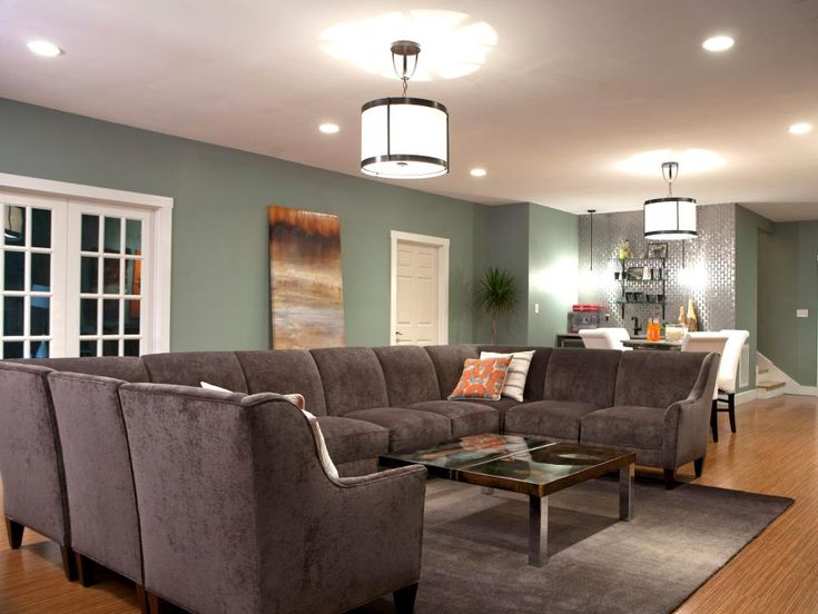 A roomy gray velvet sectional is the centerpiece of this transitional living room, which is large enough to accommodate the sizable piece of furniture. Soft green walls and smaller bar and dining areas coordinate well with the sofa for a sophisticated, practical design.