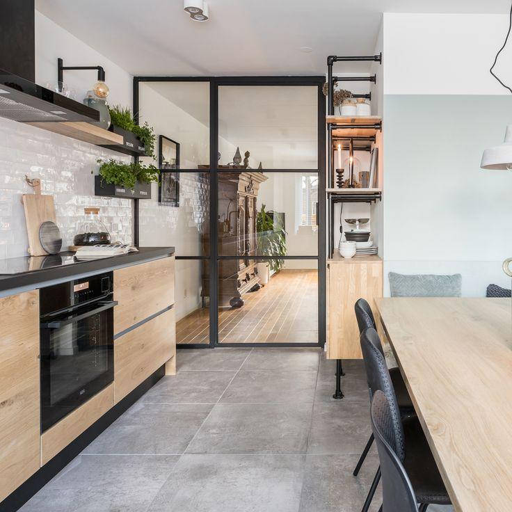 Wat voorheen nogal een oubollige ruimte was, is nu een moderne woonkeuken. Er zit een strak Scandinavisch keukenblok in, en een gezellige eethoek. Op de grond van de keuken zie je tegels met betonlook. De combinatie van hout, zwart en betontegels zorgt voor een stoere, en strakke basis. De zachtgroene kleur op de muur in de eethoek zorgt dan weer voor een gezellige toevoeging. Je ziet verder een wandkast van steigerbuizen, een eikenhouten eettafel en basic eetkamerstoelen.