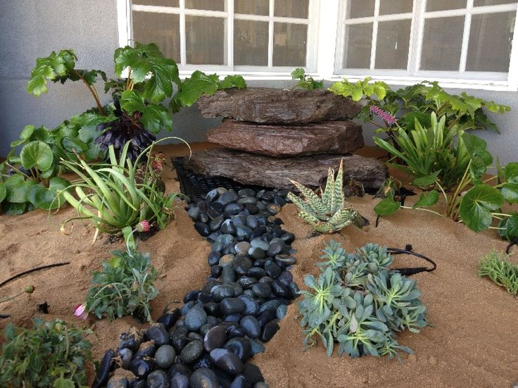 Polished Black River Rock With Plants and Brown Sands With Flowers and Stepping Stone In The Back Yard