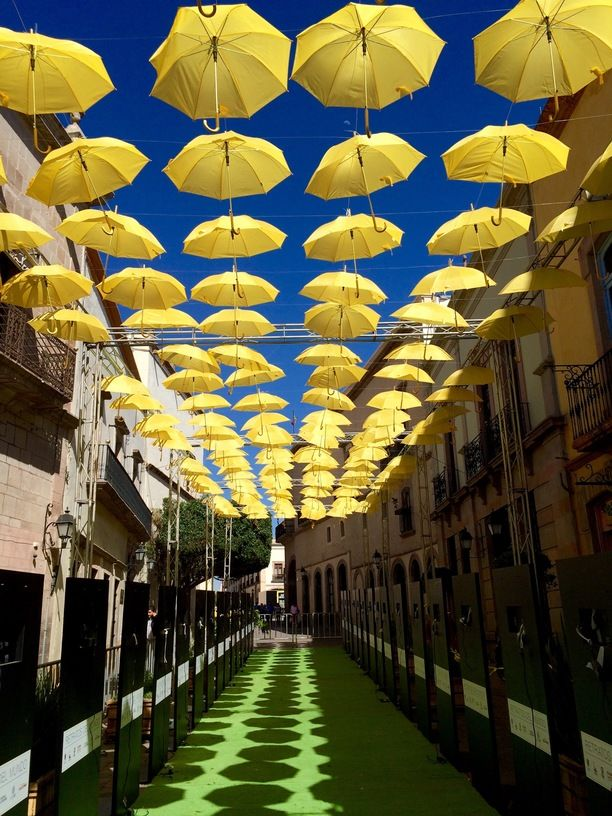 Santiago de Queretaro, Mexico — by Gareth Davies. A colorful contrast of colors and umbrellas above the streets of Queretaro marks the beginning of photofest 2015 in...