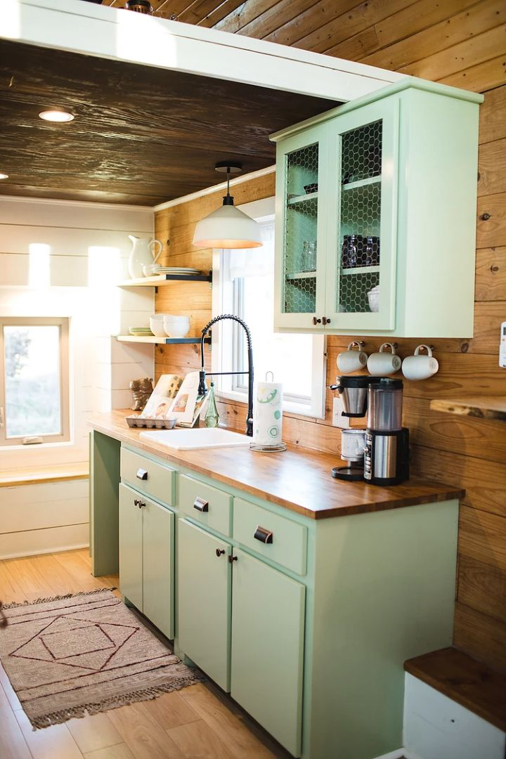 The kitchen includes a full size freestanding range, 3/4 refrigerator, and green cabinetry that matches the exterior siding. A bay window with bench storage seat creates a nice reading nook.