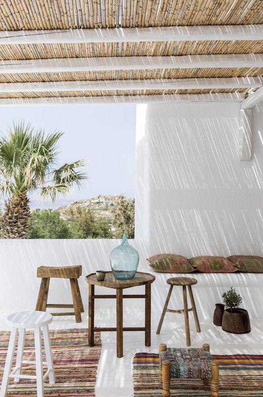 Wit Ibiza dakterras met gekleurde tapijten en krukjes van resthout. // via Mademoiselle Claudine