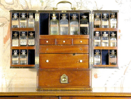 Traveling Medicine Chest, 1740-1800, mahogany, with sixteen glass bottles.  interior is fitted with blue baize lined compartments for bottles of differing sizes and six drawers fitted with compartments for bottles and pill boxes, scales, weights and other medical requisits. The whole is surmounted by a large brass carrying handle. | National Trust Collections