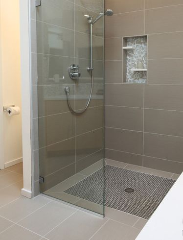 Large midcentury master bathroom in Seattle with a curbless shower, gray tile, white walls and porcelain floors.  Smaller glass mosaic tiles were used on the shower floor to maximize grout coverage for increased slip resistance.