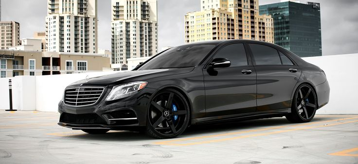 Customized Mercedes-Benz S550 with blacked out exterior trim, smoked lights, painted blue brake calipers, and lowered on color matched 22″ XO Luxury wheels.