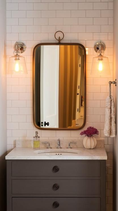 Exquisite bathroom features a nook filled with a subway tiled accent wall lined with a gray single vanity topped with carrera marble under a curved brass hook mirror illuminated by glass wall sconces.