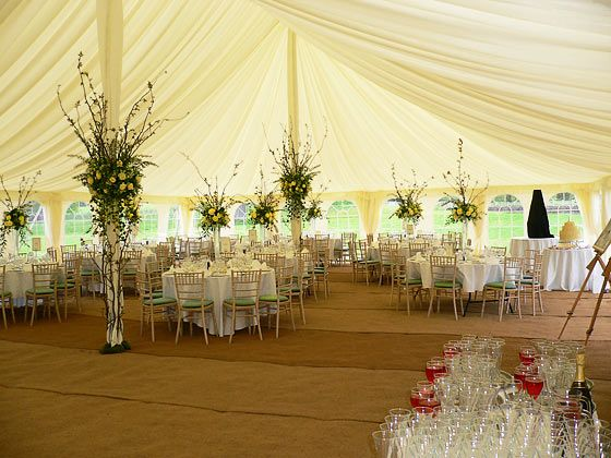 Pretty floral pole decoration inside a traditional wedding for Indoor marquee decoration