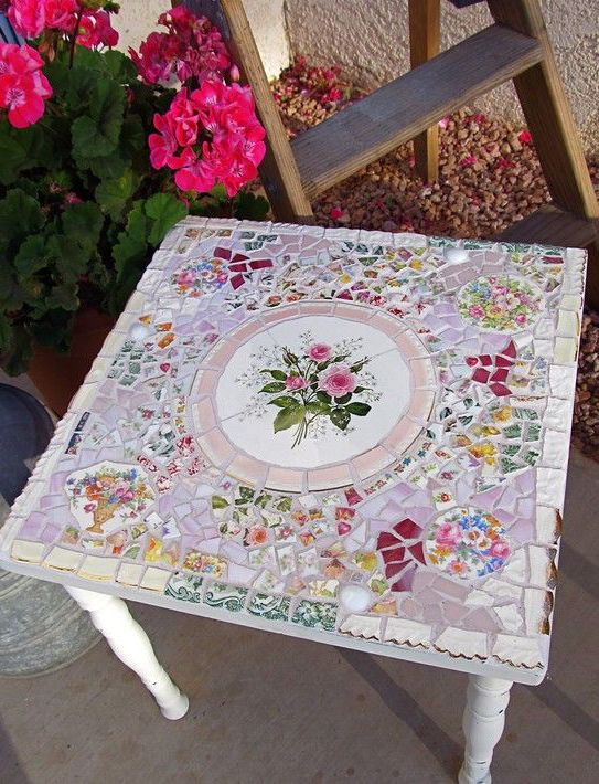 Want to turn your side table from a simple accessory into a statement piece? Cover its surface in a pretty mosaic of broken china dishes.  Learn more at 2ndTimeAroundMosaics.   - CountryLiving.com
