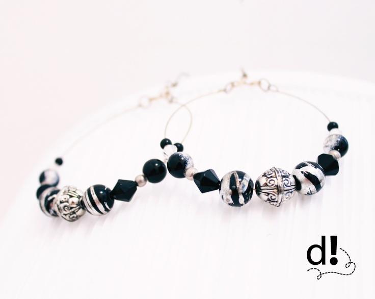 Argollas con piedras de vidrio en color negro combinados con líneas en plata y cuentas en color plata · $5