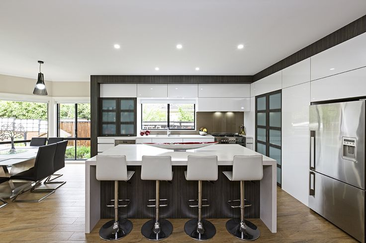 This Summit Kitchens contemporary kitchen design starts with the dark feature frame that surrounds the entire room.  The rich wood grain imitation beautifully contrasts with the glossy white of the cabinetry, instantly drawing the eye and keeping it there.