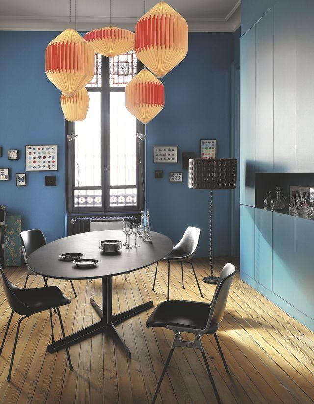 Salle à manger au mobilier noir et suspensions aux teintes colorées