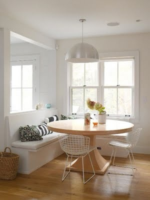 banquette seating in a dining area with round table and classic Bertoia chairs