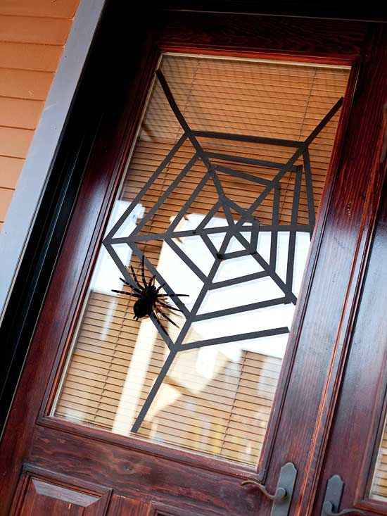 Webbed Window Covering using black tape and a rubber spider.  Need to do this or the window monsters for the porch