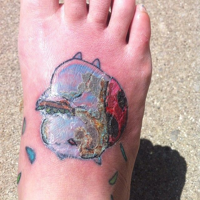 And this is an improvement /: this quick photo is the most sun my foot has seen in almost 2 weeks and today has been the first day I've been able to wear a shoe comfortably and walk unaided. Seriously NOT looking forward to touching this one up. This has been my first ever #infectedtattoo and I'm pretty bummed about it. #catbughasmange #zombiecatbug #scabby #gross #ouchmotherfucker