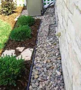 A rock maintenance strip around the house ... catches splashes, keeps siding clean and minimizes pests. Put your foundation plantings in front of the strip... so what I NEED to do!!!!