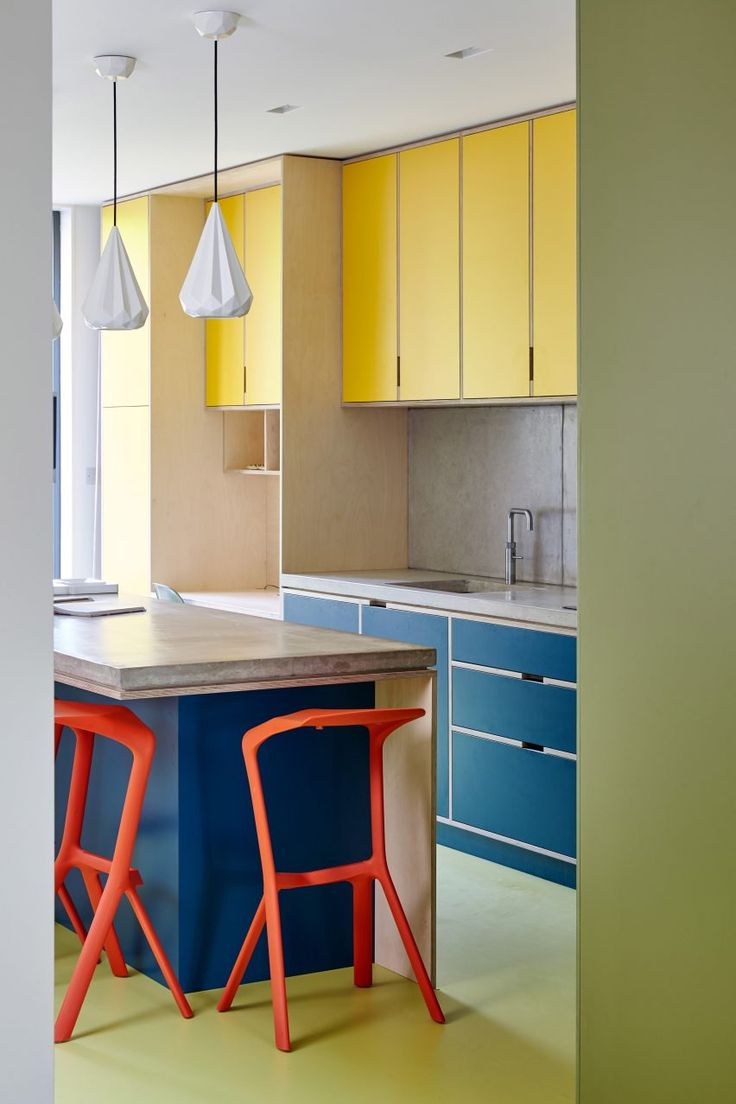 In this kitchen concrete countertops and splashbacks rest on top of birchwood cupboards with navy accents to contrast with the yellow kitchen wall units.