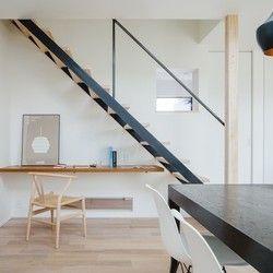 素材感を活かした鉄の黒皮仕上げの鉄骨階段。踏板のみの階段で空間が広く見え、足下のスペースを利用してパソコンコーナーを造作。キッチンと統一してチーク材で壁持ち出しのデスクを仕上げた。 | 八日市の家