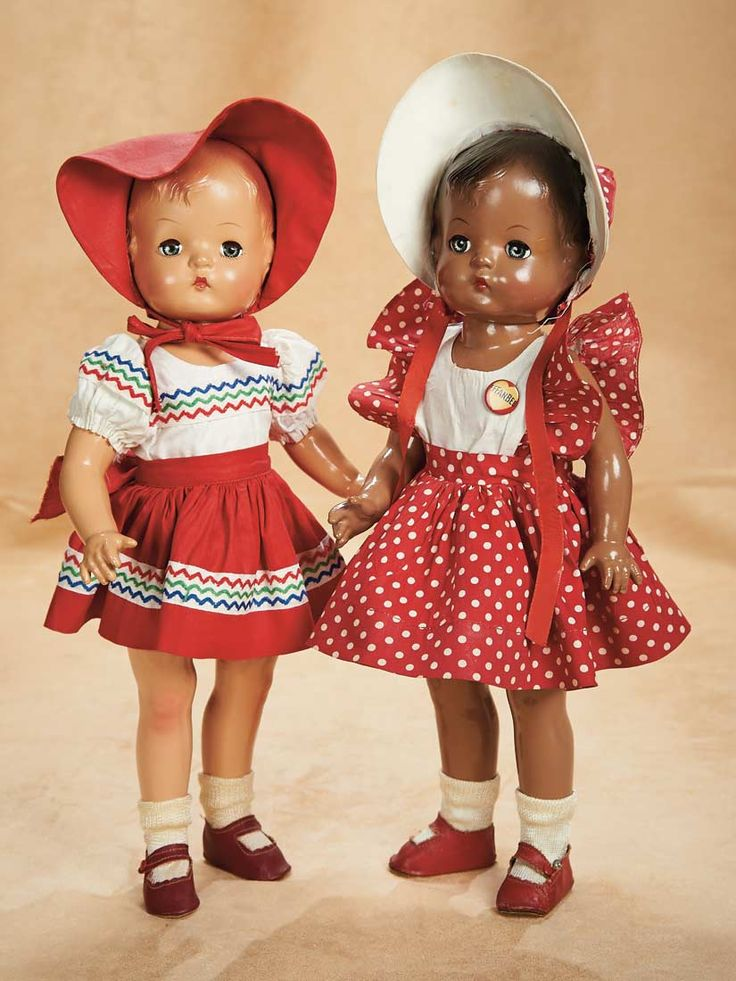 """14"""" white and black variations of the Patsy doll, United States, 1946, by Effanbee Doll Co.  While earlier black Patsy dolls (called """"Patsy-Joan"""" in Effanbee literature) were simply brown-painted variations of the white doll's molding, this year's version was a re-designed model with details of curly hair atop the doll's cherubic head, reflecting a more accurate understanding of the characteristics of actual black children."""