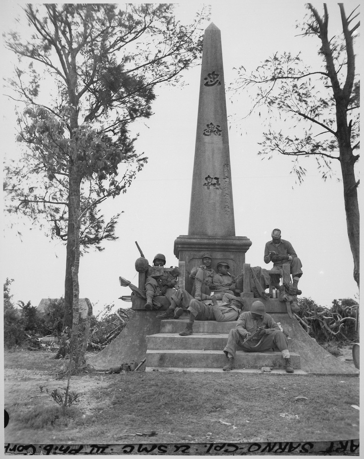 """""""Marines, following the rapid Japanese retreat northward on Okinawa, pause for a moments rest at the base of a Japanese war memorial. They are (on steps) Pfc. F. O. Snowden; Navy Pharmacist's Mate, 2nd class R. Martin; (on monument, left to right) Pvt. J. T. Walton, Pvt. R. T. Ellenberg, Pfc. Clyde Brown, Pvt. Robb Brawner. Photo was taken during the battle for Okinawa."""", 04/12/1945"""