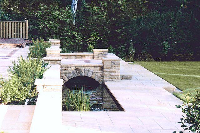 Evolving Spaces Landscape Designs LTD - A feature bridge across formal pond leading to a lawned area.