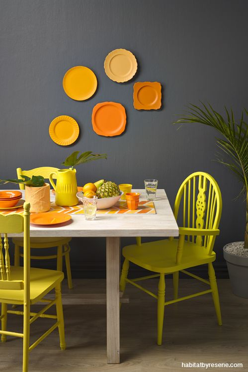 Take mismatched chairs and paint in similar Resene yellows - Resene Wild Thing (at back), Resene Bright Lights (side) and Resene Teddy (front). A grouping of old plates has been painted in a variety of oranges – from bottom left clockwise, Resene Juicy (two plates), Resene Touche, Resene Clockwork Orange and Resene Adrenalin. The palm pot is in Resene Transmission, the floor is in Resene Colorwood Whitewash.
