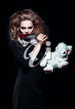 Horror shot: a scary monster girl with torn rabbit toy and bloody knife in hands